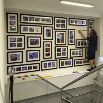 Hanging frames over a staircase